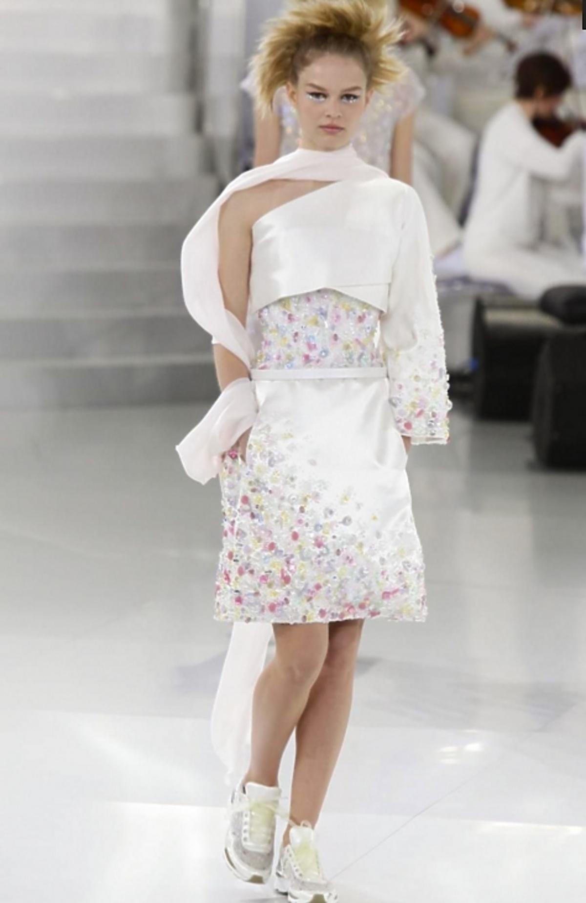 Modelka w białej sukience z taśmą i koralikami na wybiegu