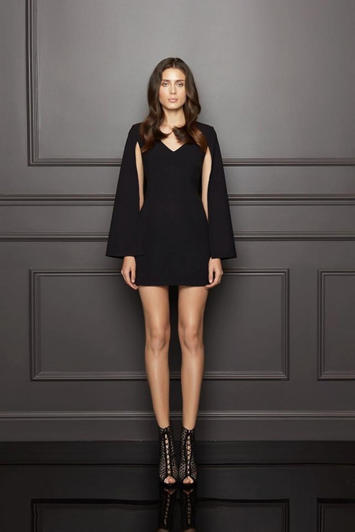 Modelka w czarnej sukience mini z szerokimi rękawami