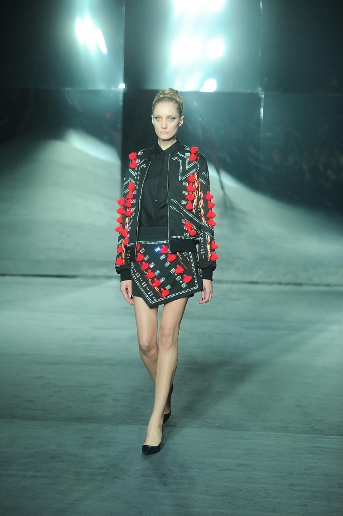 Modelka w czarno-czerwonej bluzie z kryształami i spódnicy od Mariusza Przybylskiego