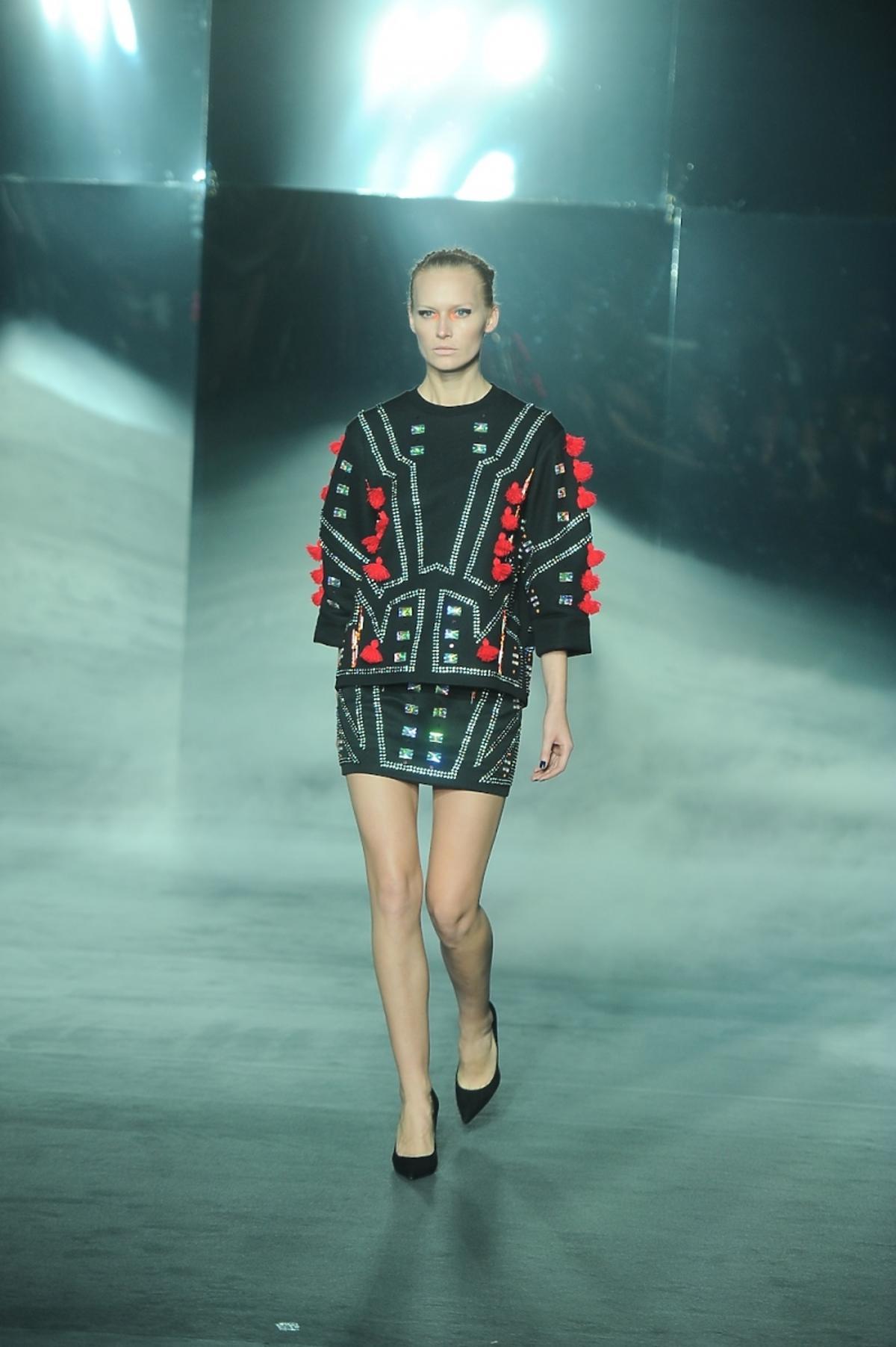 Modelka w ozdobnej czarno-czerwonej bluzie Mariusza Przybylskiego