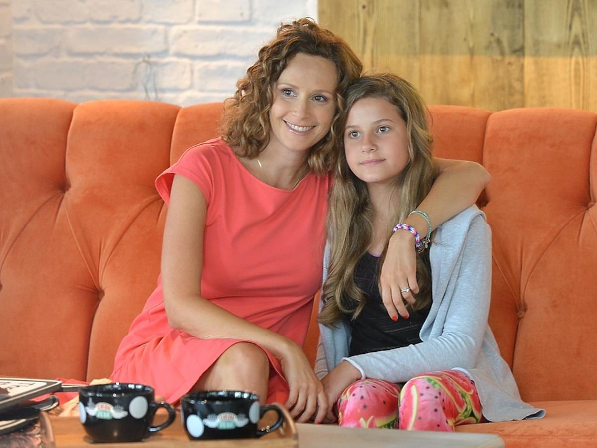 Monika Mrozowska z córką na pomarańczowej kanapie