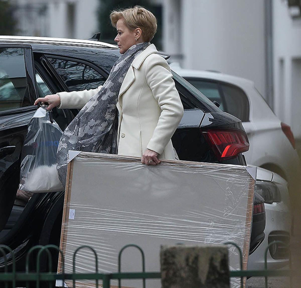 Monika Zamachowska w białym płaszczu niesie obraz