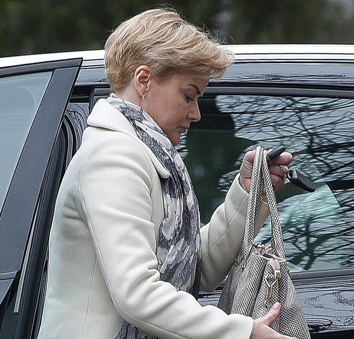 Monika Zamachowska w białym płaszczu wsiada do samochodu