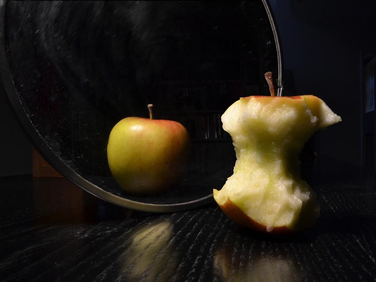 Nadgryzione jabłko przegląda się w lustrze, w którym widzi owoc o okrągłych kształtach.