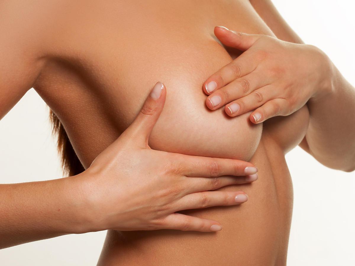 Naga kobieta wykonująca masaż piersi