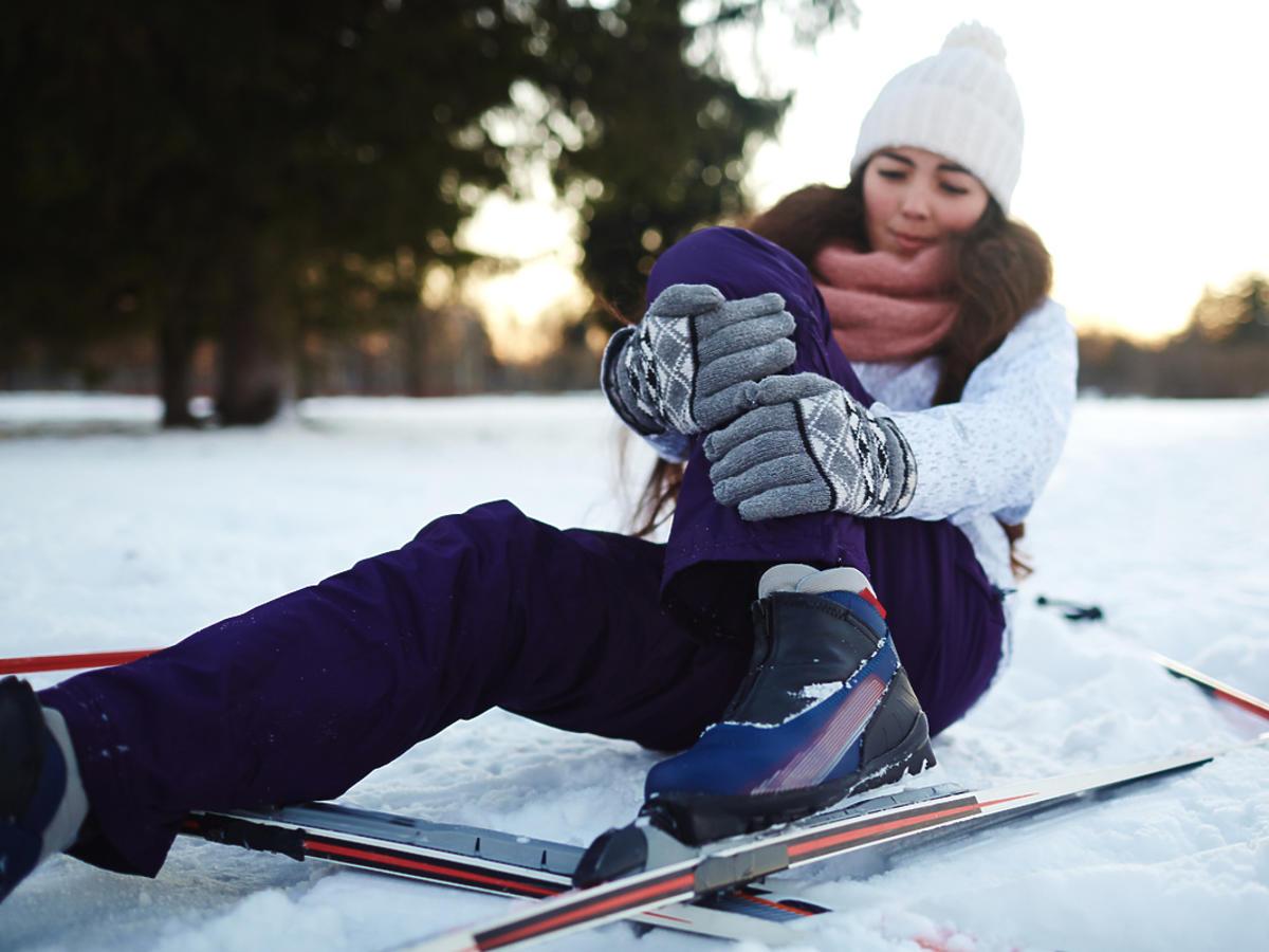 Narciarka leży na śniegu i trzyma się za nogę.