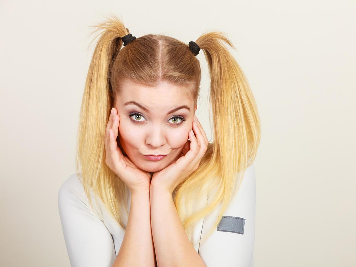 Nastolatka uśmiecha się, jest uczesana w dwa kucyki.