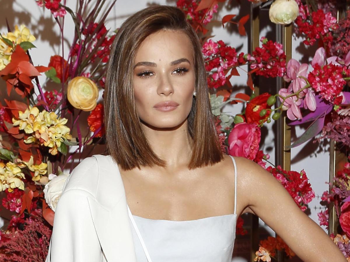 Natalia Szroeder w białej sukience na tle kwiatowej ścianki