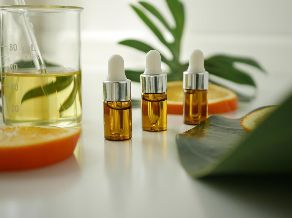Naturalne olejki o właściwościach antybakteryjnych stoją na stole w szklanych butelkach.