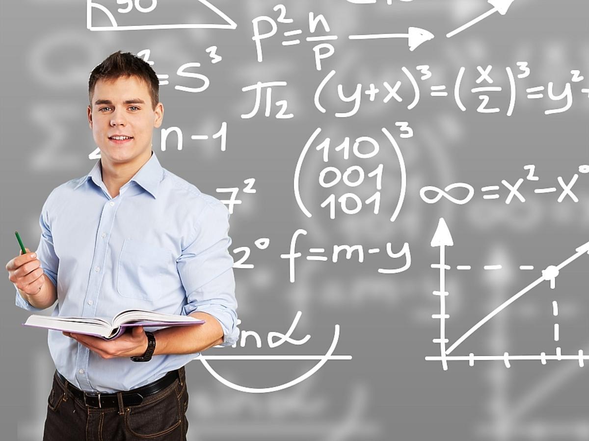 nauczyciel przy tablicy z książką w ręku
