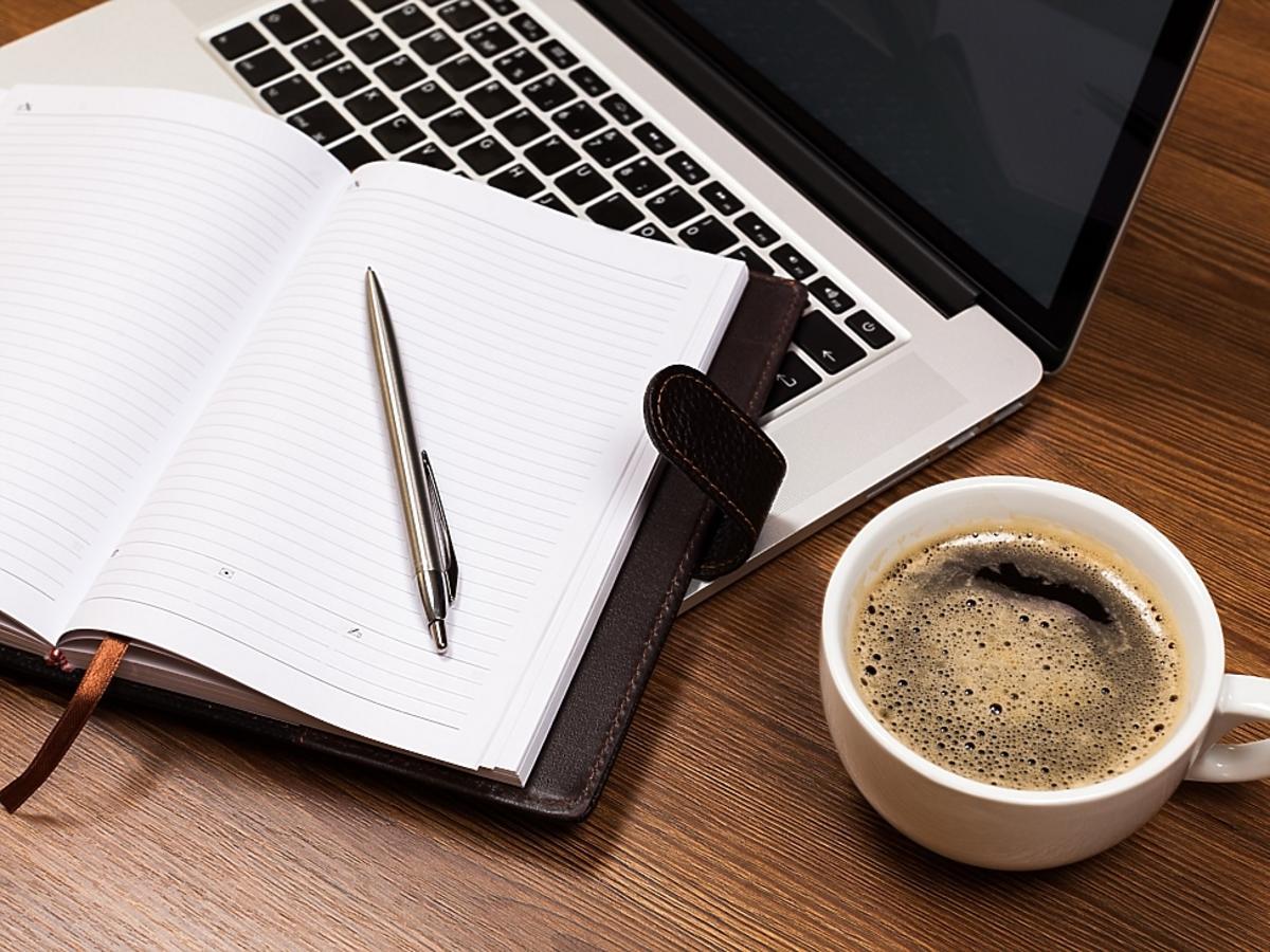 Notes, komputer, kawa i pióro.