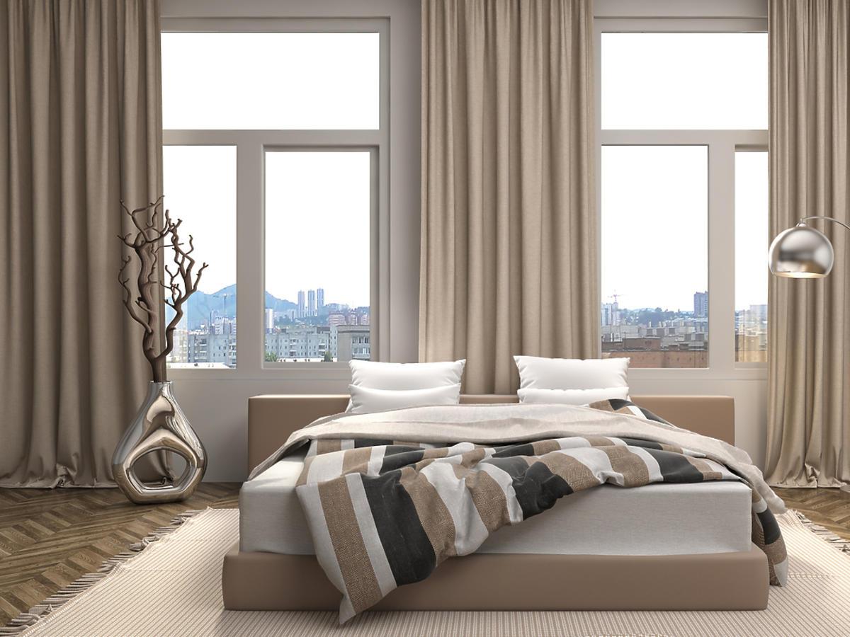 Nowoczesna sypialnia urządzona w odcieniach beżu i brązu.