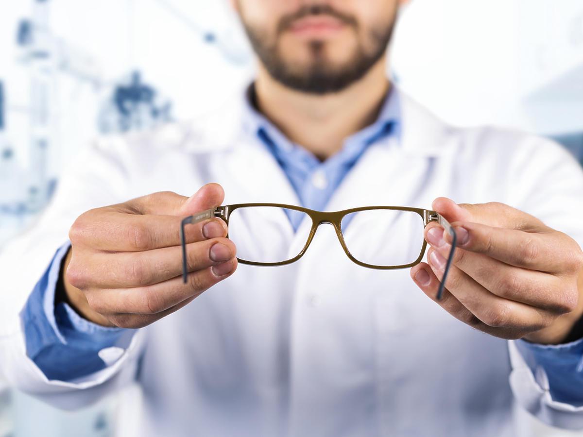 Okulista przymierza pacjentowi okulary korekcyjne.