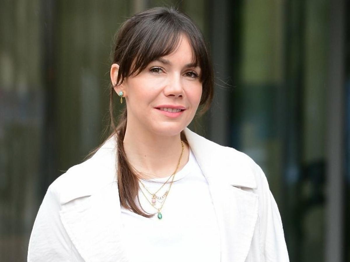 Olga Bołądź w białej bluzce i jasnym płaszczu
