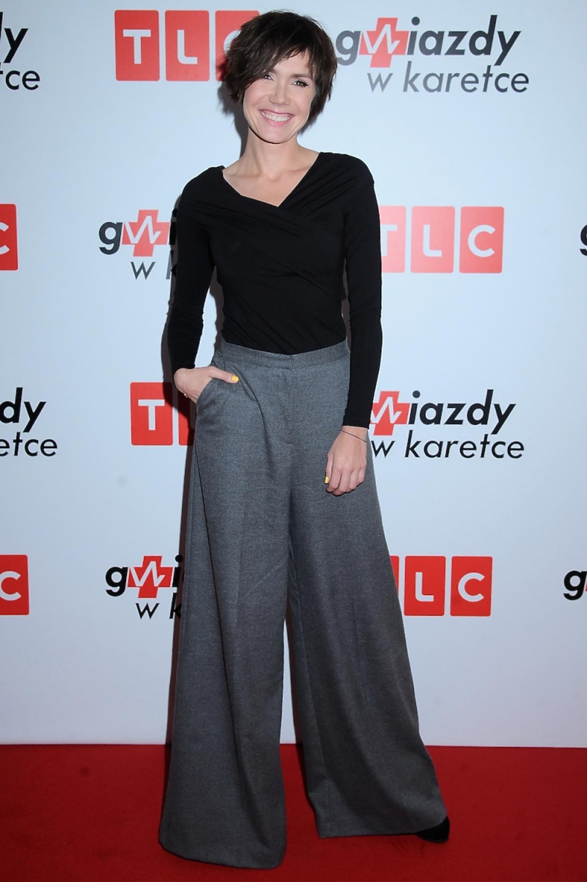 Olga Bołądź w szerokich szarych spodniach, czarnej bluzce na czerwonym dywanie