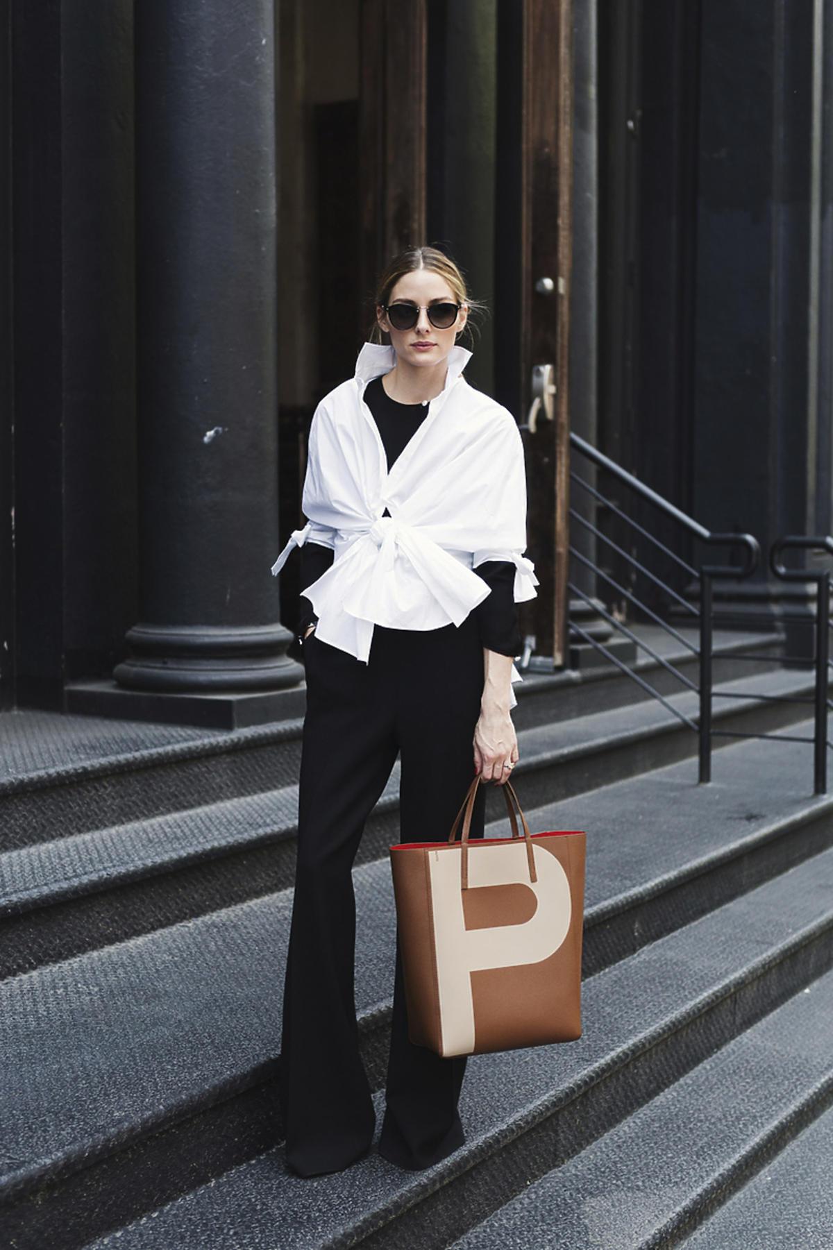 Olivia Palermo w czarnych spodniach, koszuli i z brązową torbą