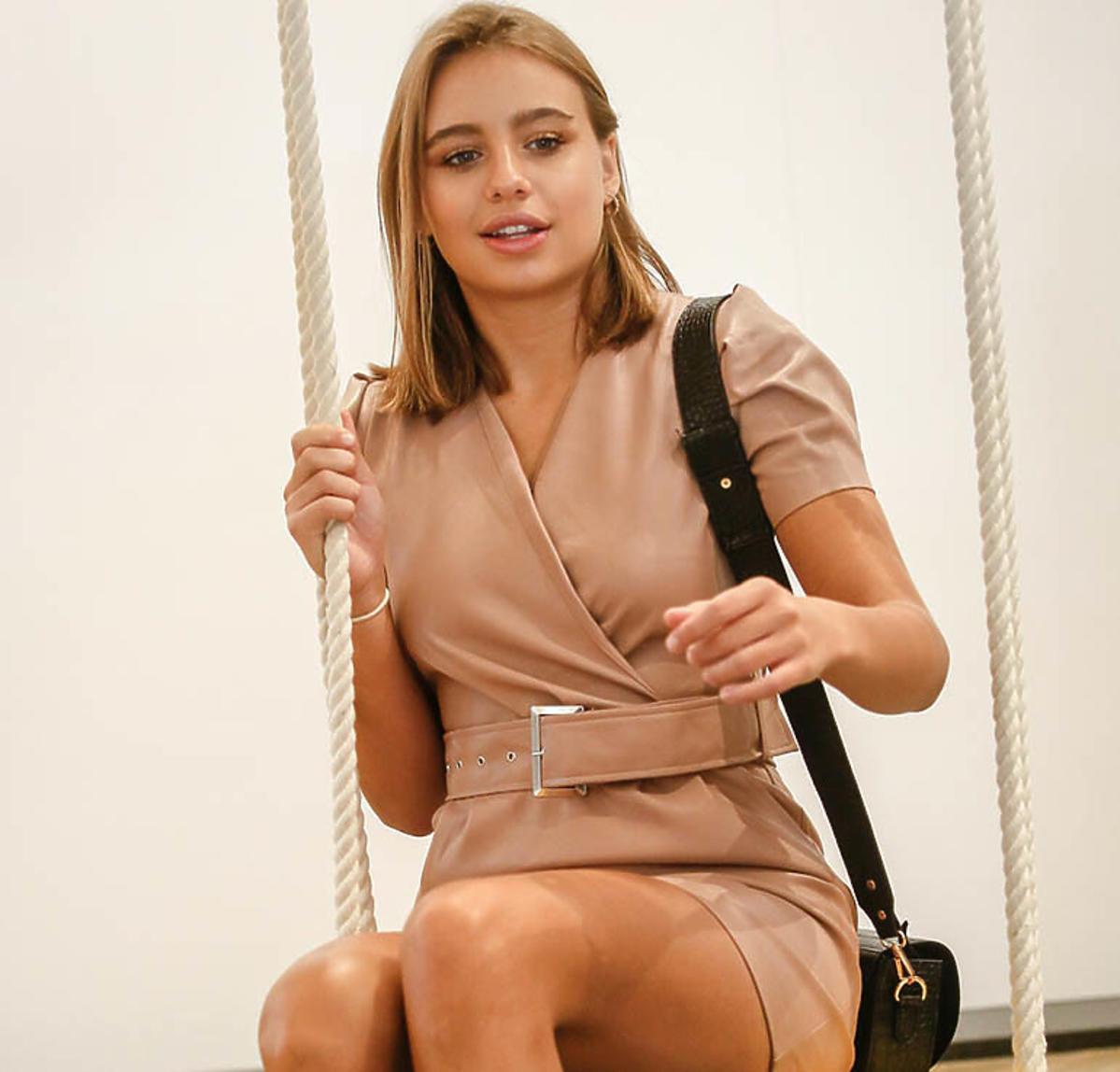 Oliwia Bieniuk w beżowej sukience siedzi na huśtawce