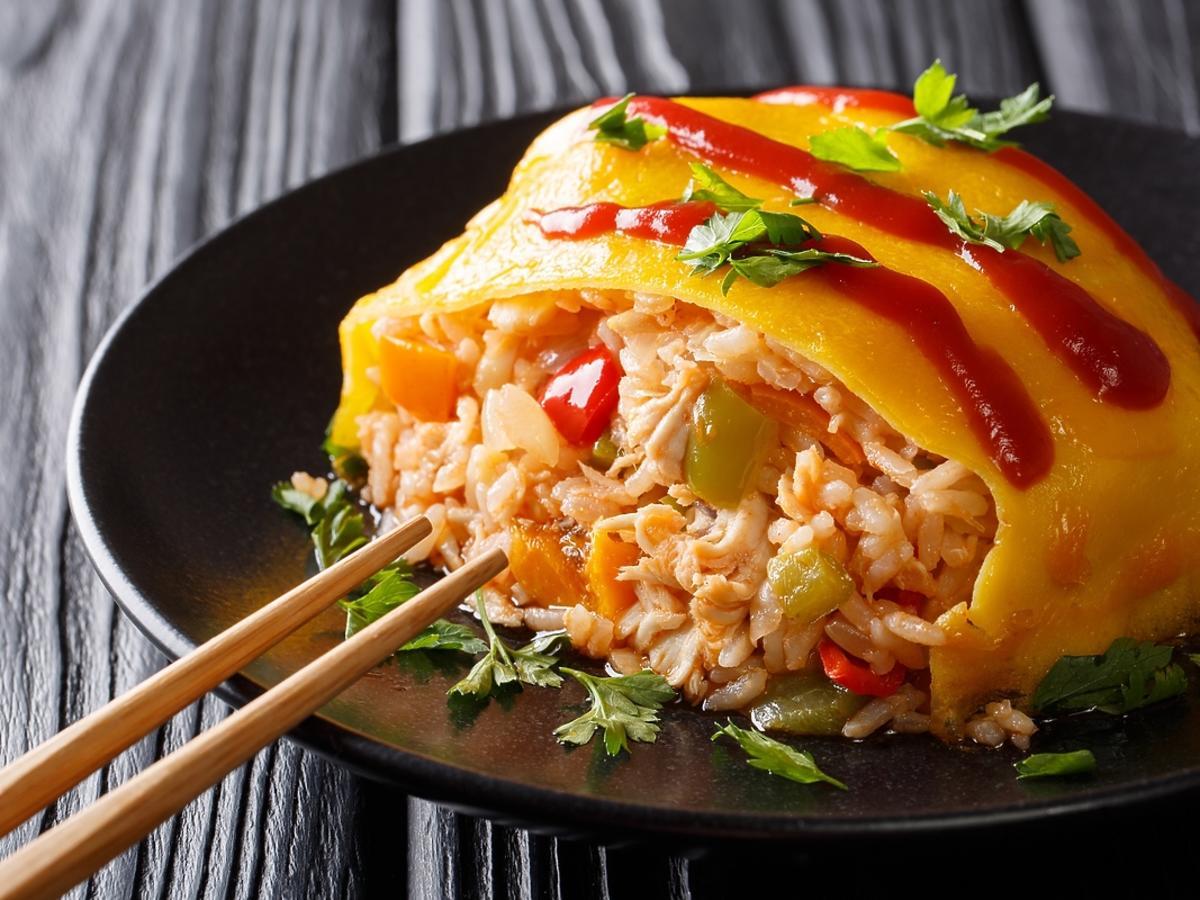 omlet z ryżem, warzywami i kurczakiem na czarnym talerzu
