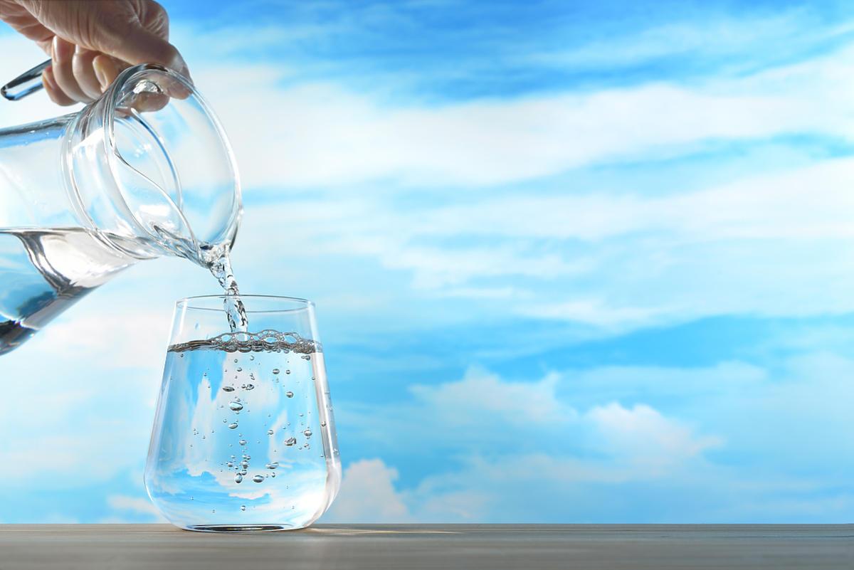osoba nalewająca wodę do dzbanka