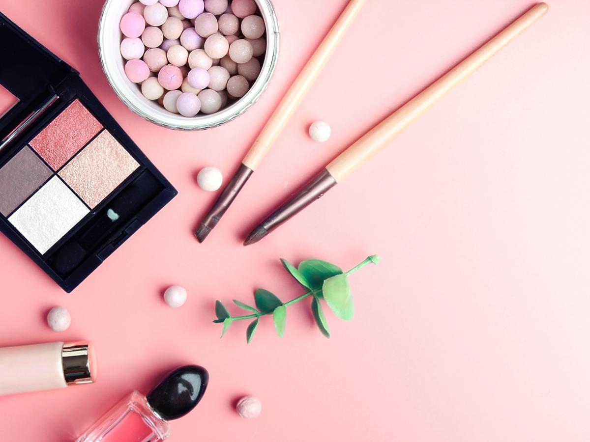 paleta z cieniami do powiek, błyszczyk, puder w kulkach na różowym tle