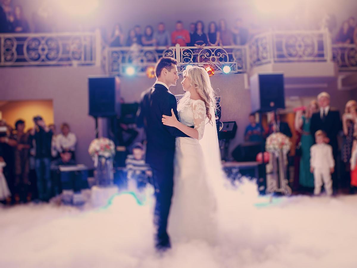 Para młoda tańczy na środku parkietu podczas wesela.