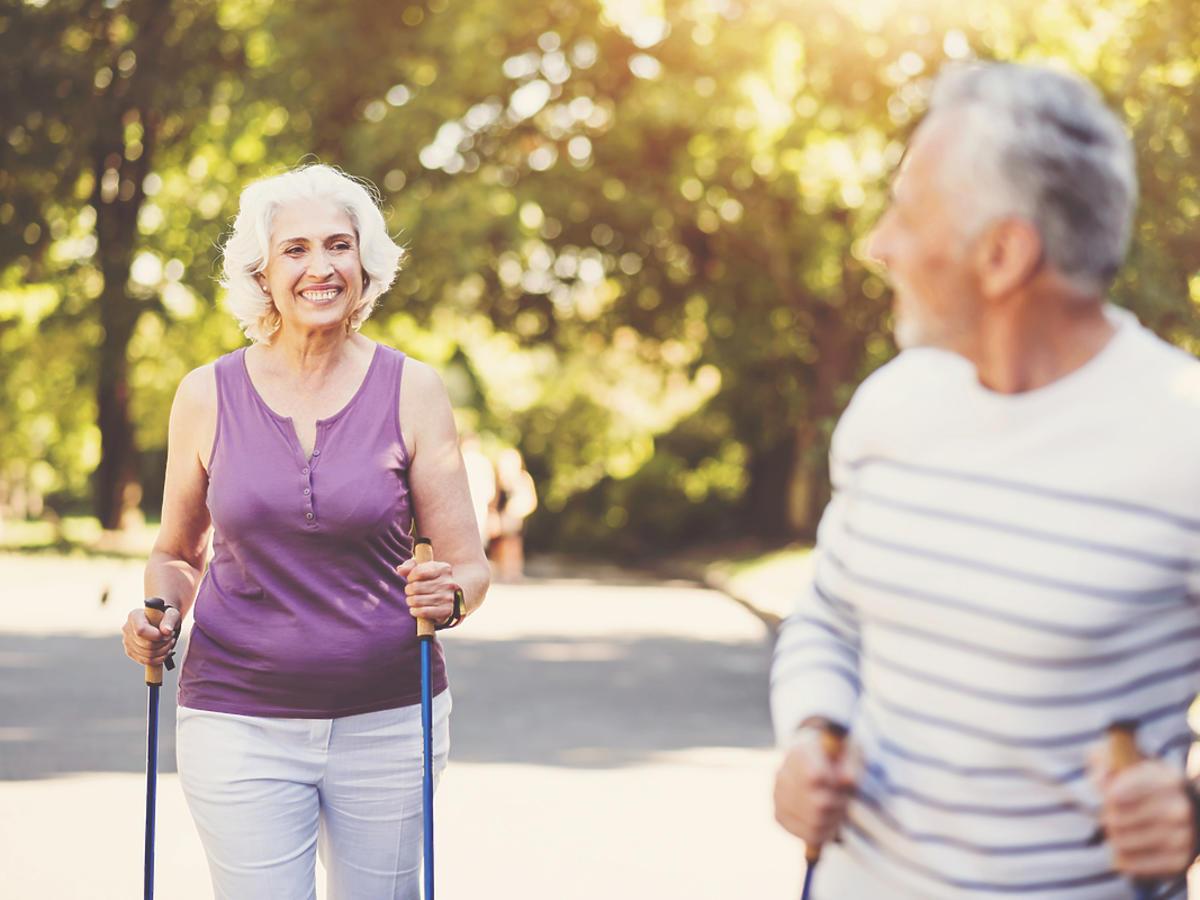 Para seniorów spaceruje po parku z kijkami.