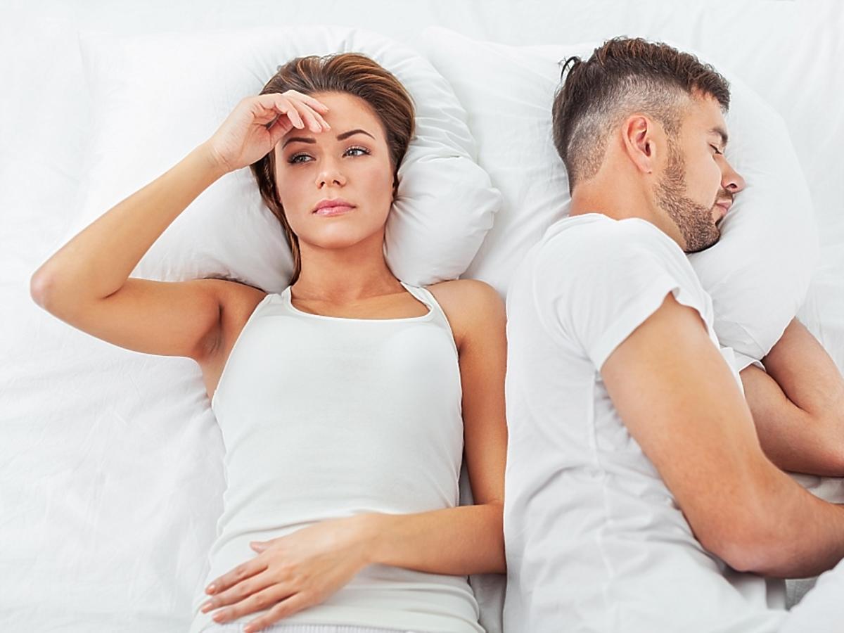 para w łóżku mężczyzna śpi, kobieta jest zmartwiona