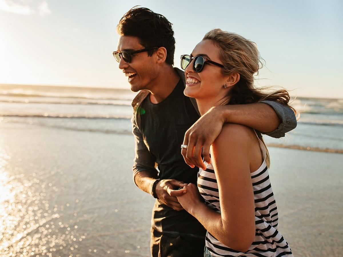 Para zakochanych spaceruje brzegiem morza.