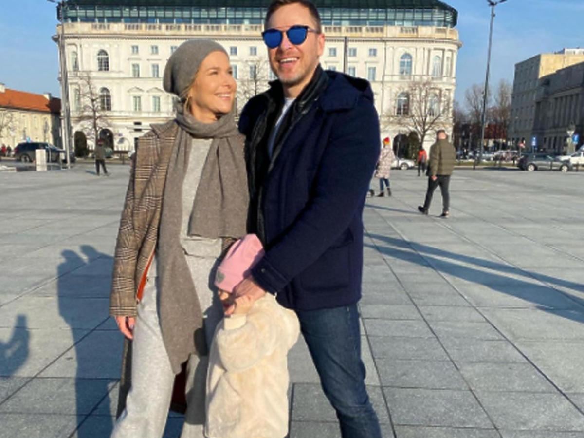 Paulina Sykut-Jeżyna z mężem i córką pozują do zdjęcia na pl. Piłsudkskiego w Warszawie