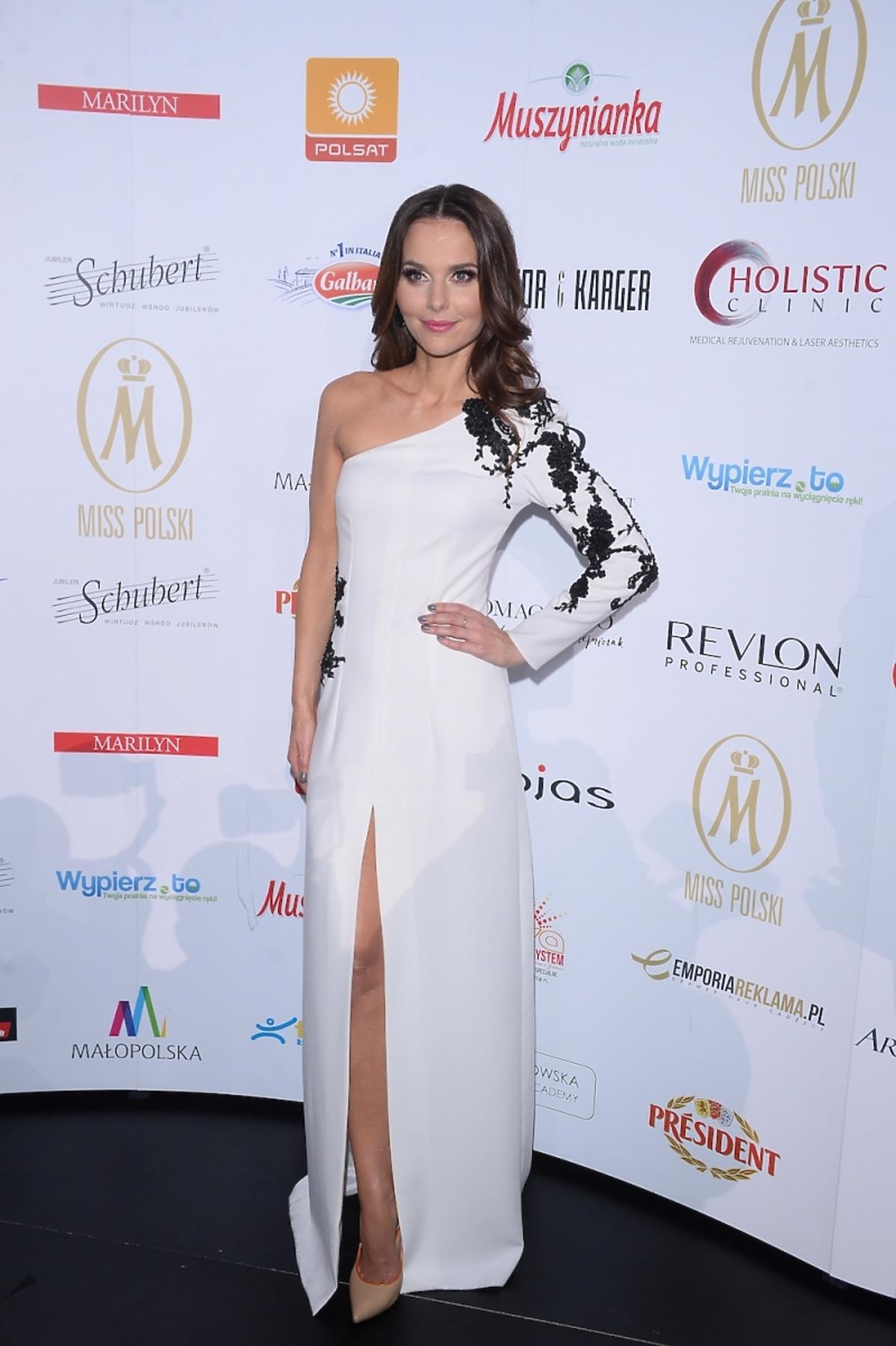 Paulina Sykut w białej długiej sukni ozdobionej czarną koronką na ramieniu