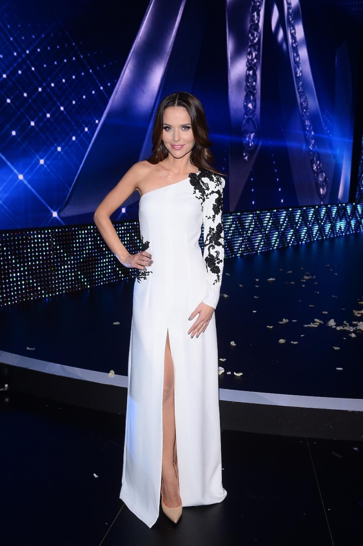 Paulina Sykut w białej długiej sukni z rozporkiem i czarną koronką