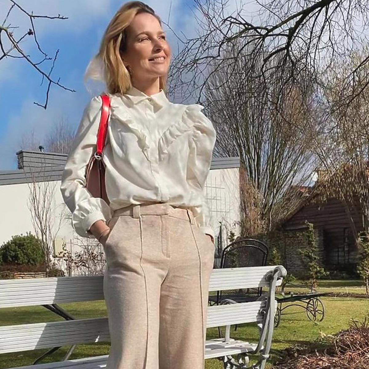 Paulina Sykut w białej letniej bluzce z falbankami i bufkami i beżowych spodniach
