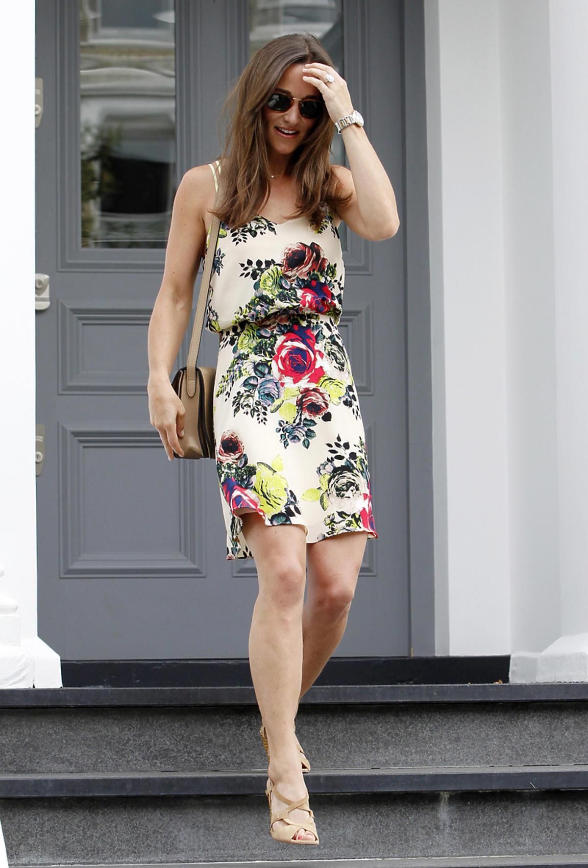 Pippa Middleton w białej sukience z kolorowymi kwiatami schodzi po schodach