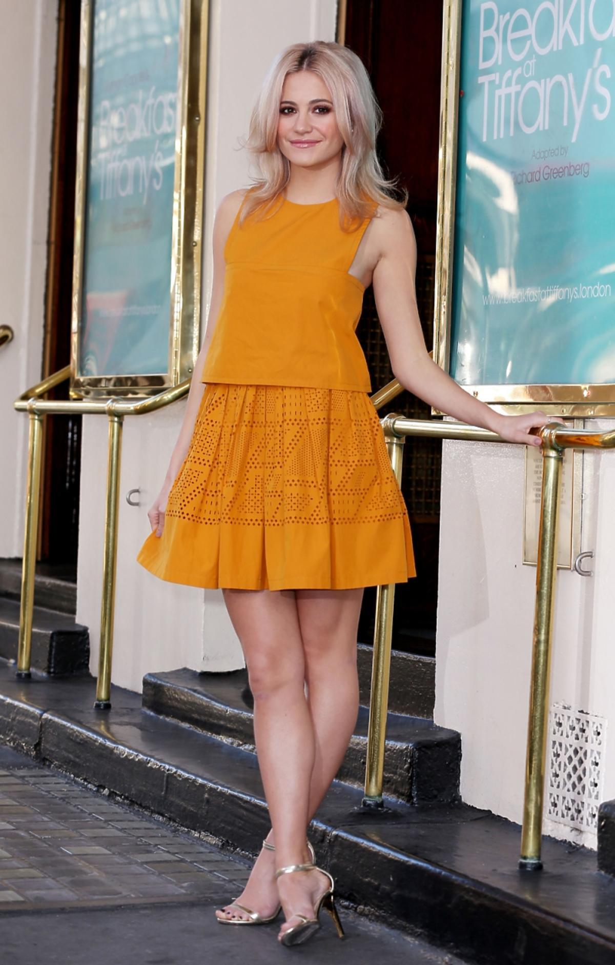 Pixie Lott w żółtej sukience przed budynkiem teatru