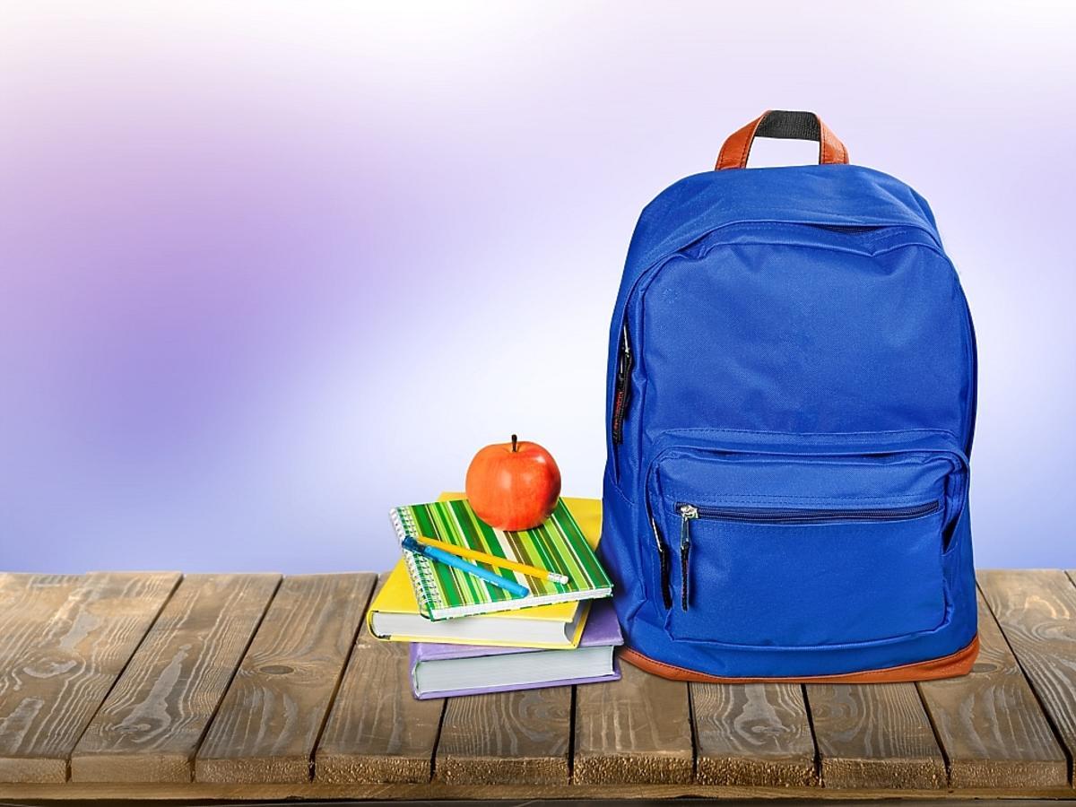 plecak z książkami i jabłko