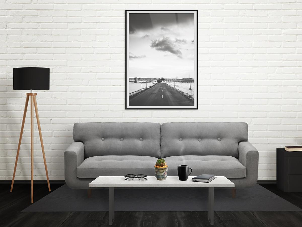 Pokój, na ścianie obraz, obok lampa stojąca, na podłodze kanapa.