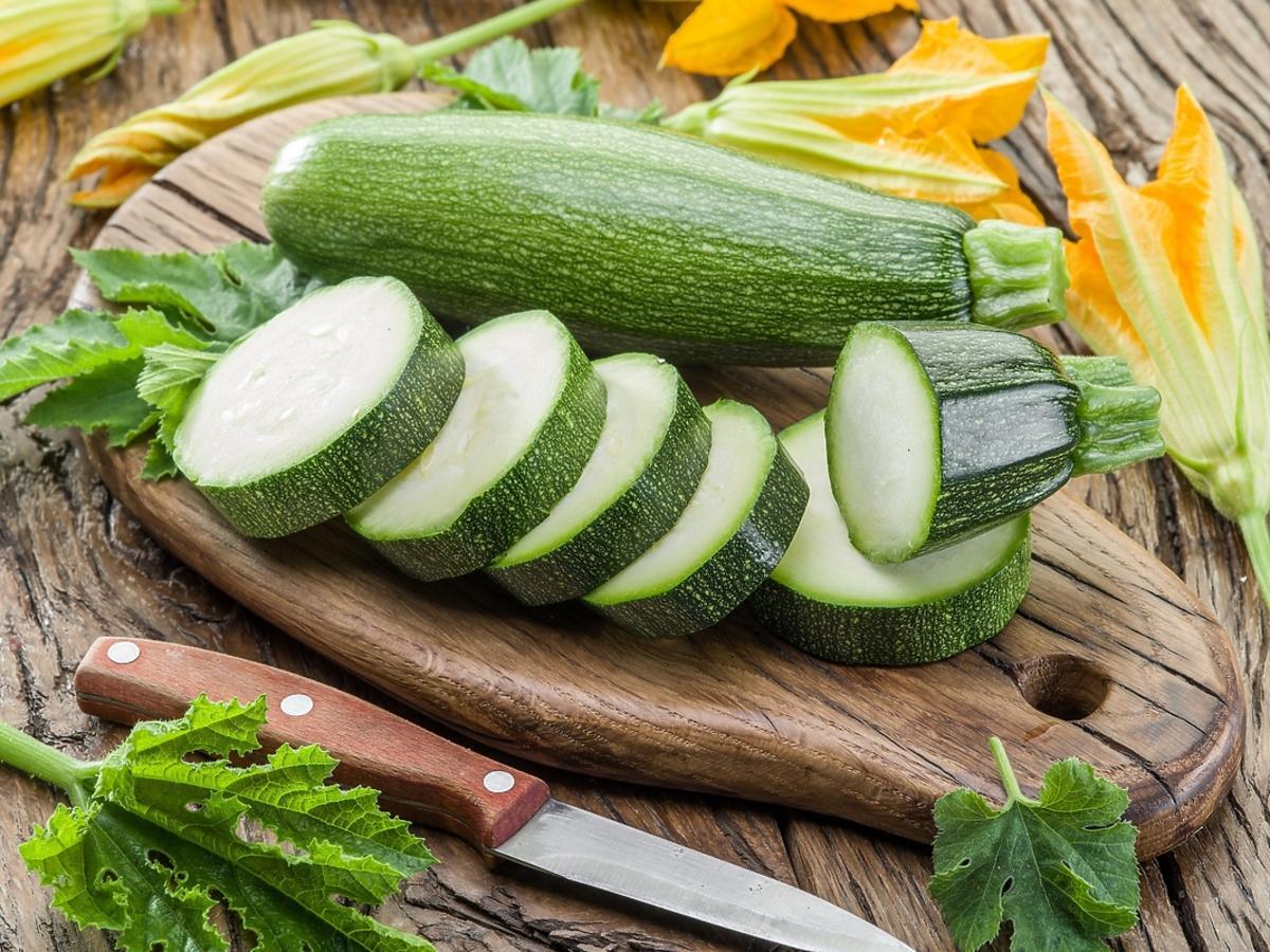 pokrojona zielona cukinia leżąca na brązowej desce