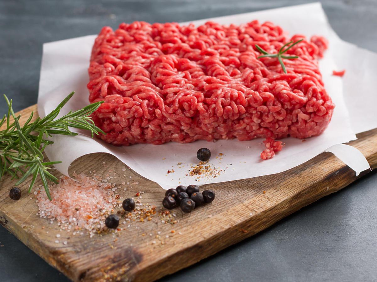 Pół kilograma mięsa mielonego leży na desce do krojenia