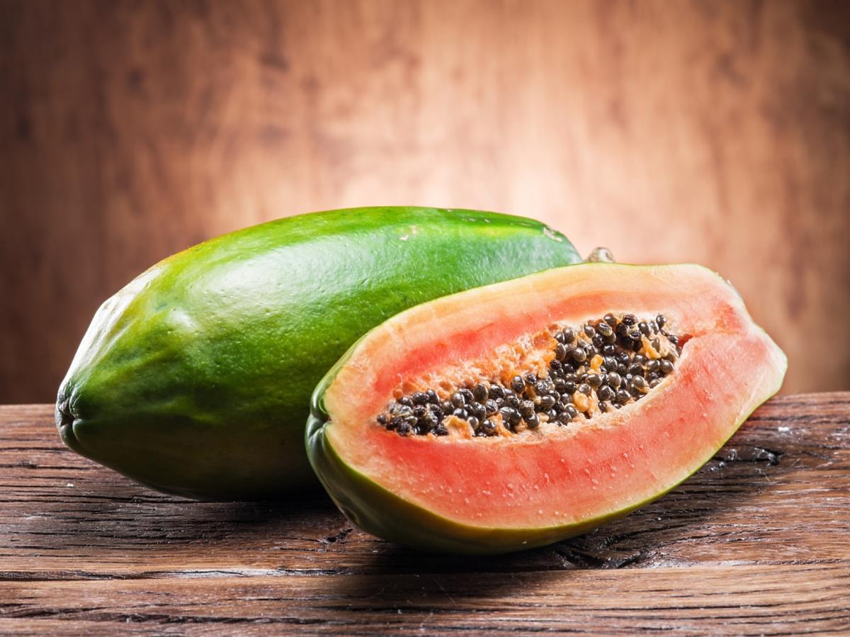 Przepołowiony owoc papai na drewnianej desce