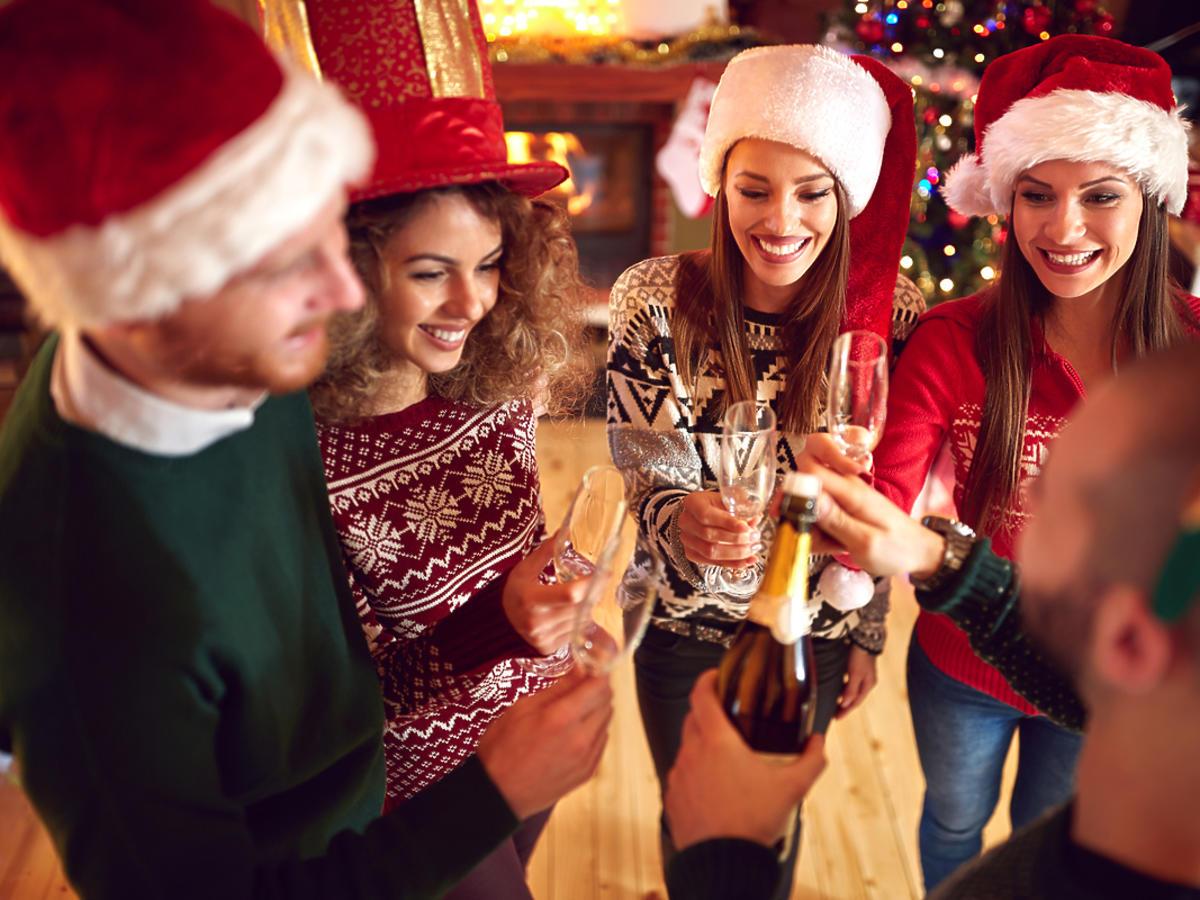 przyjaciele stukają się lampkami z szampanem w Sylwestra