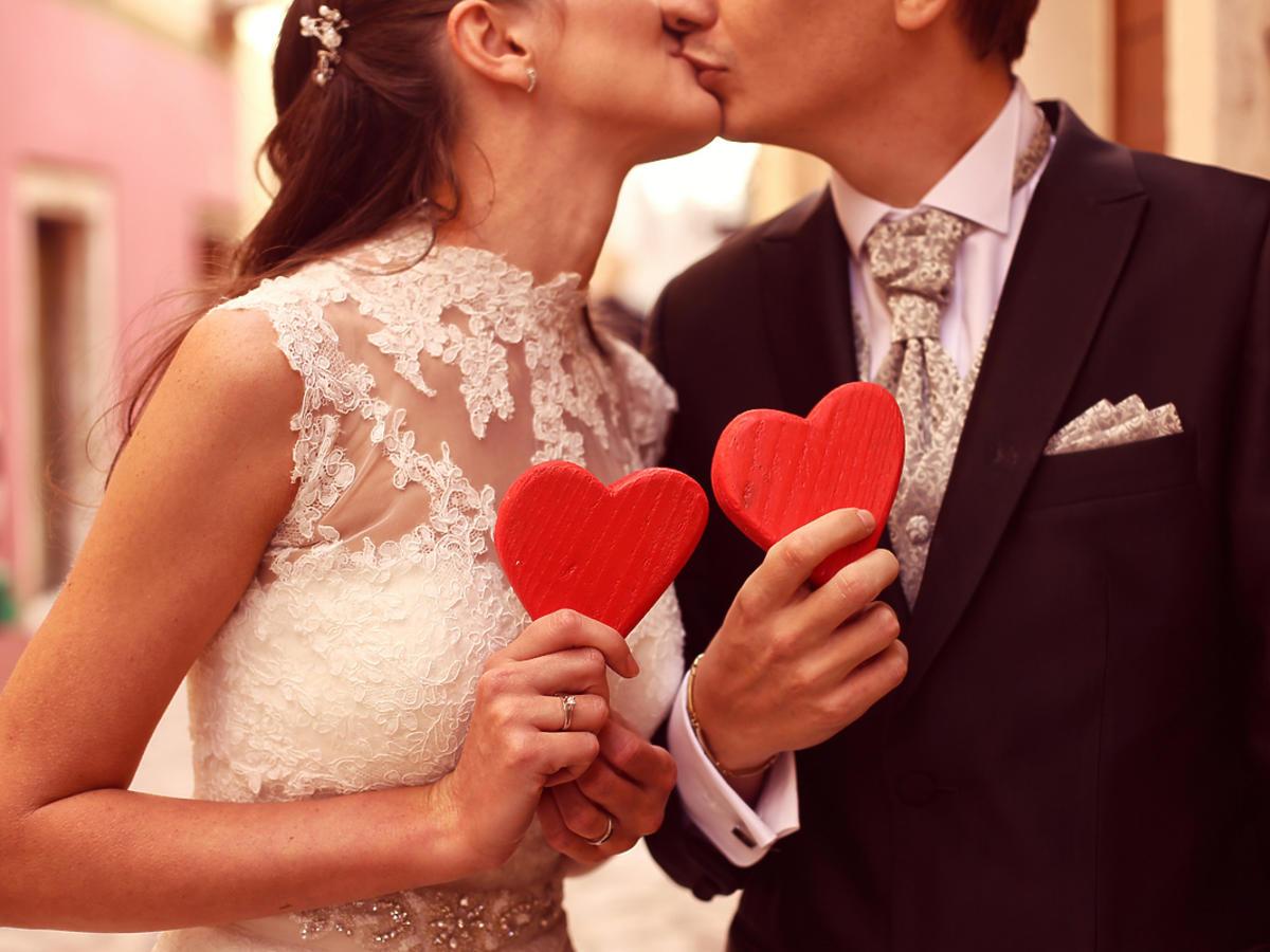 Przyszli małżonkowie całują się trzymając w dłoni czerwone serca