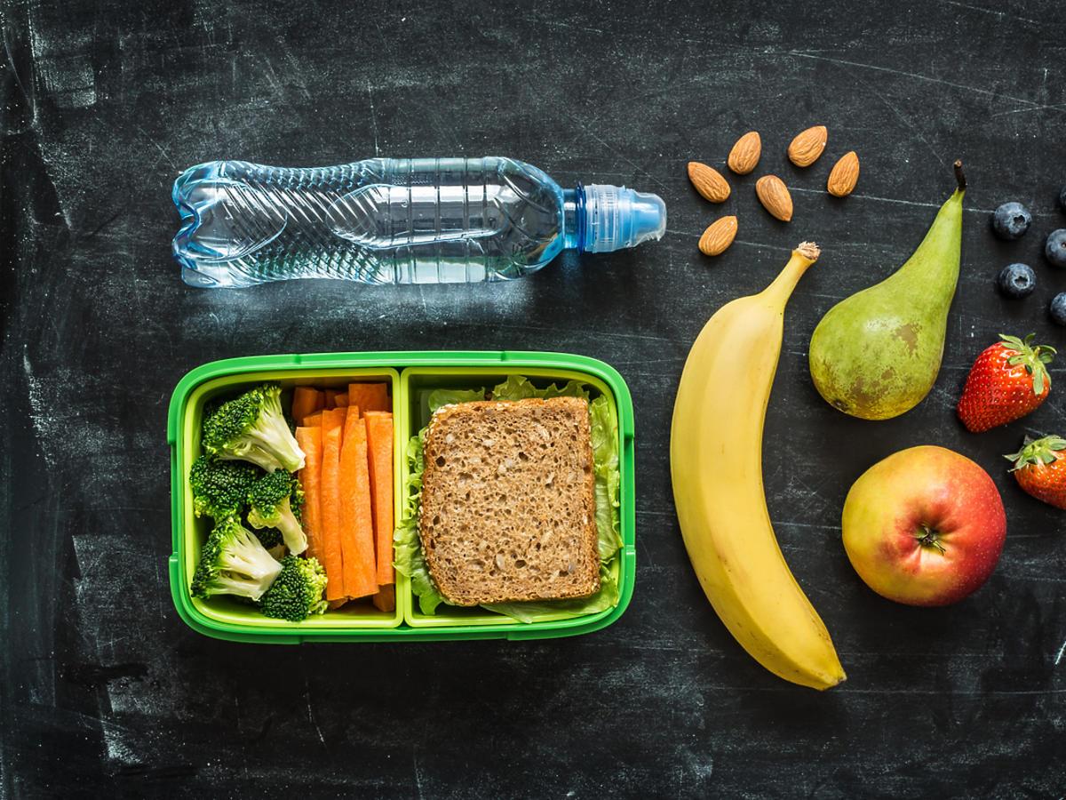 Pudełko na lunch, w środku warzywa i kanapka. Obok świeże owoce i butelka wody.