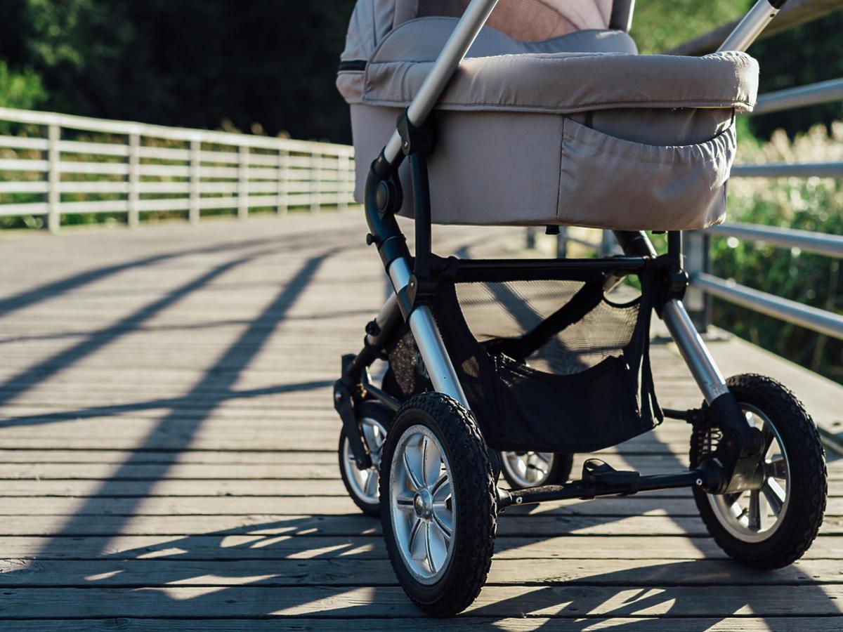 Pusty wózek dla dziecka stoi na zewnątrz.