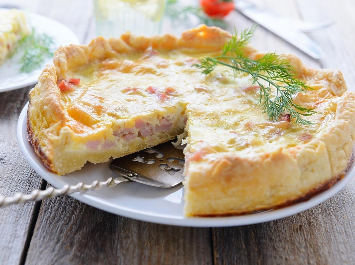 quiche z warzywami i łososiem na białym talerzu