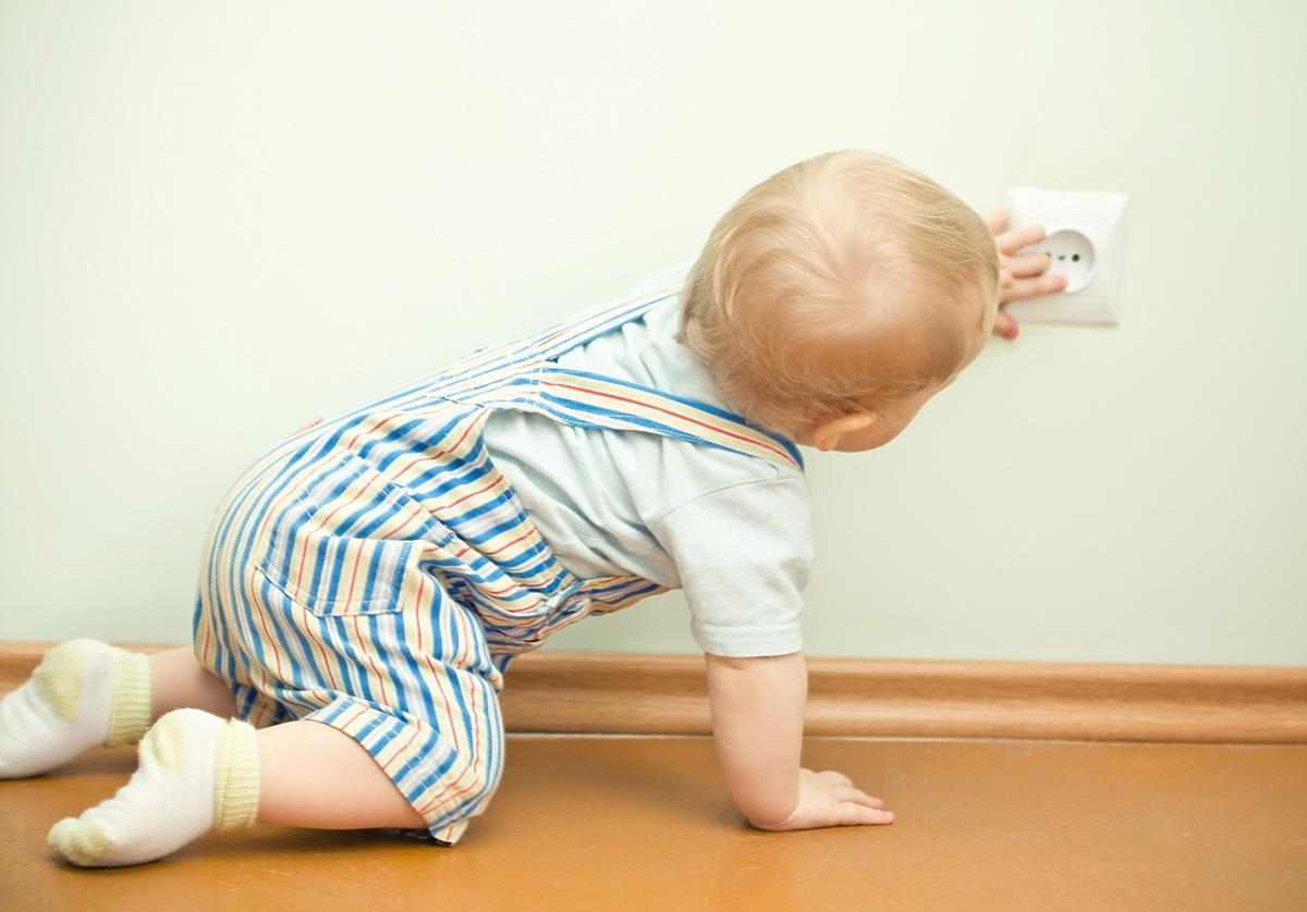 raczkujące dziecko dotyka paluszkami kontaktu