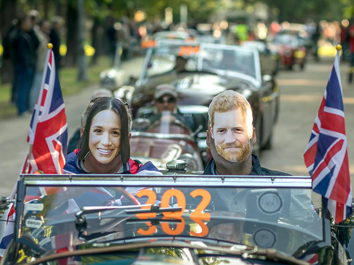 """Rajd """"Mille Miglia"""", zdjęcie z trasy - kierowca i pilot w maskach Meghan i Harry'ego"""