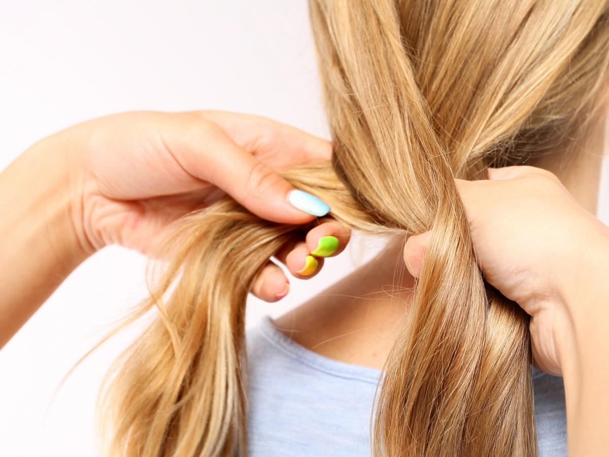 Ręce zaplatające długie włosy