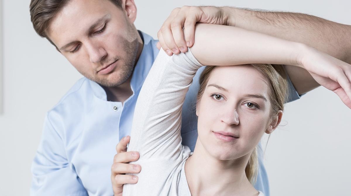 rehabilitant pomaga pacjentce z urazem łokcia