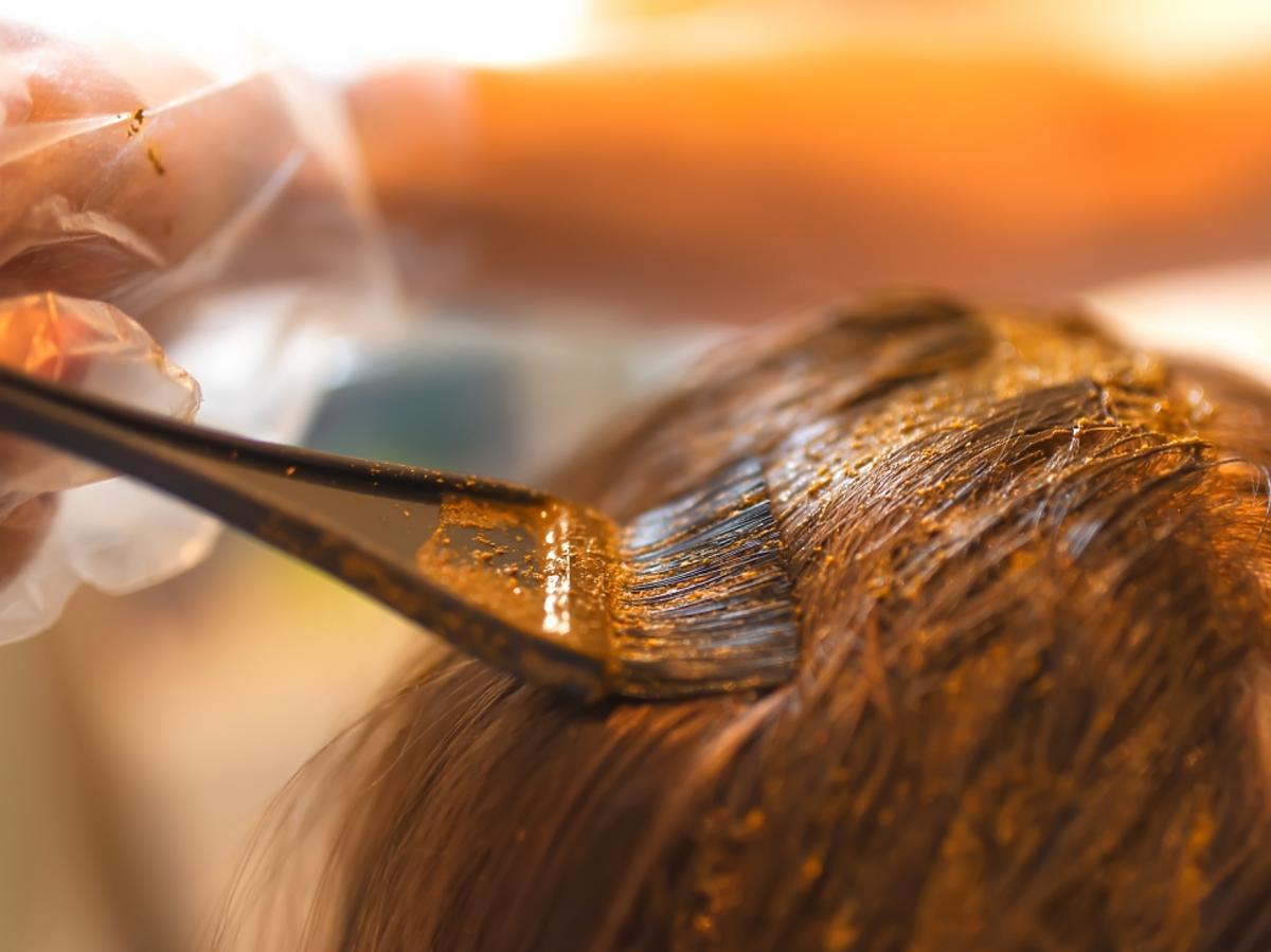 Ręka farbująca pędzelkiem włosy naturalną henną