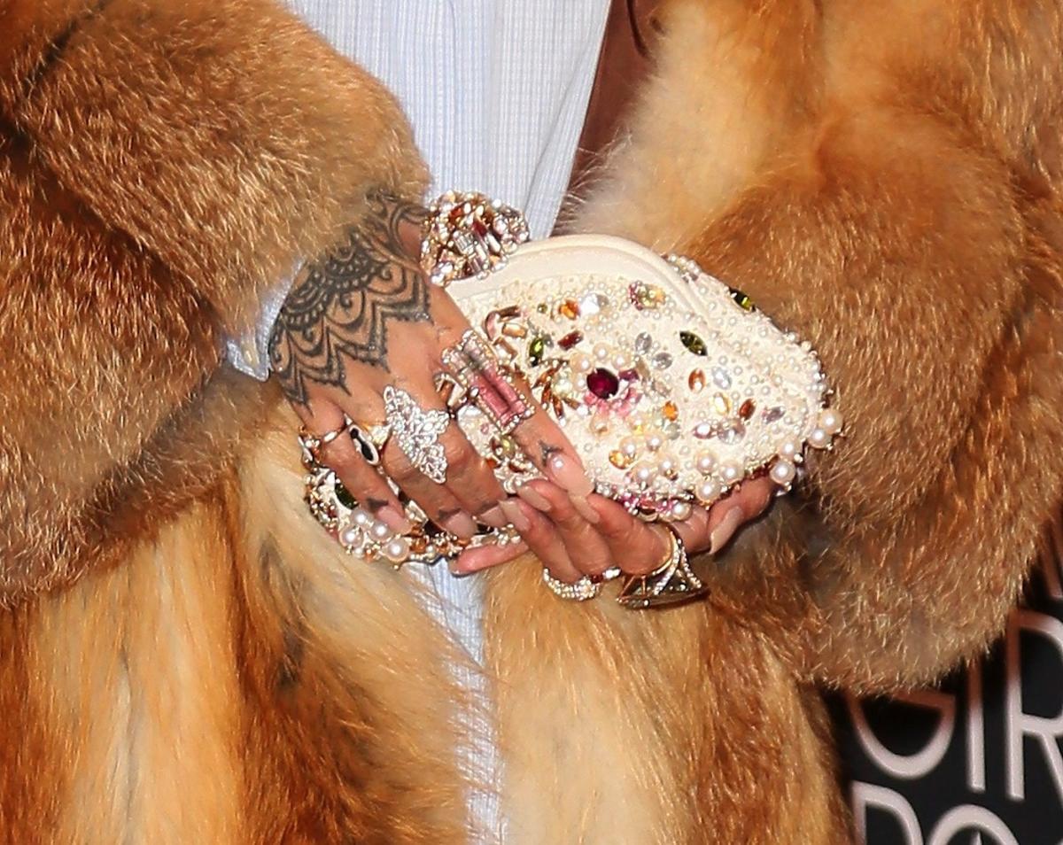 Rihanna w futrze i ze złotymi ozdobami we włosach i z torebką ozdobioną kryształkami